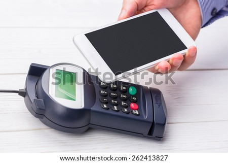 Man using smartphone to express pay on a wooden table - stock photo