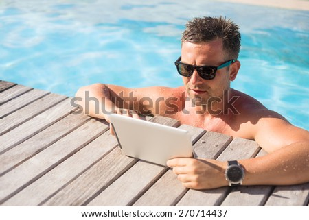 Man using tablet computer while relaxing in the pool - stock photo