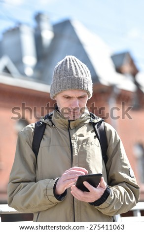 Man using tablet outdoors in a sunny spring day - stock photo