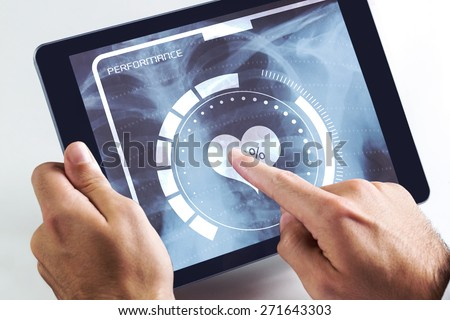 Man using tablet pc against medical interface on xray - stock photo
