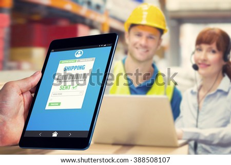 Man using tablet pc against smiling businesswoman wearing headset using laptop - stock photo