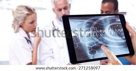 Man using tablet pc against three doctors using a tablet - stock photo