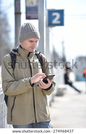 Man using tablet while waiting the train on a railroad station platform - stock photo