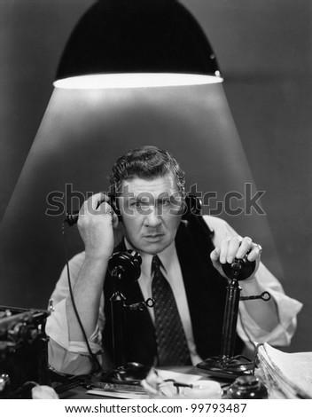 Man using two telephones - stock photo