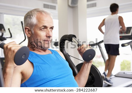 Man Using Weights Machine With Runner On Treadmill In Background - stock photo