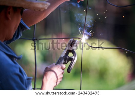 Man using welding metal cage fence. - stock photo