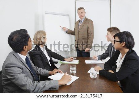 Man using whiteboard in business meeting - stock photo