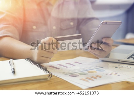 Man verifies account balance on smartphone with mobile banking application.Online payment, hands holding a credit card and using smart phone for online shopping,selective focus,vintage color - stock photo