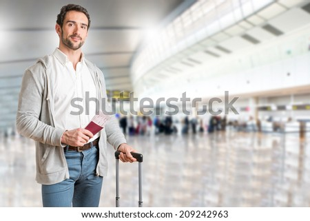 Man waiting at an airport, holding tickets, in an airport - stock photo