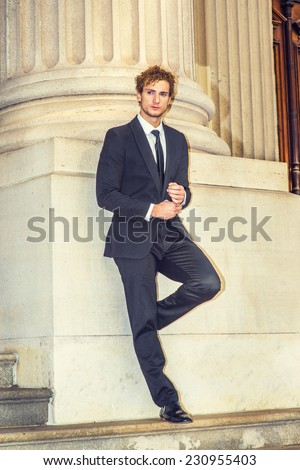 Man Waiting for You. Dressing in black suit with Shawl Lapel, black necktie, a young sexy guy with curly hair is standing by column outside office, a hand touching a cuff of sleeve, thinking. - stock photo