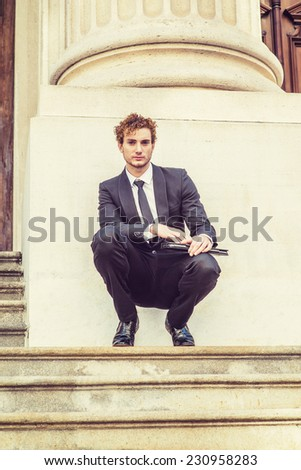 Man Waiting for You. Dressing in black suit with Shawl Lapel, black necktie, a young sexy guy with curly hair is squatting on stairs outside office, holding a laptop computer, relaxing.  - stock photo