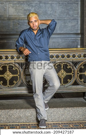 Man Waiting for You. Wearing a blue shirt, gray pants, casual shoes, a young guy with beard, yellow hair is standing by old fashion style railing in a hallway, looking at you.  - stock photo