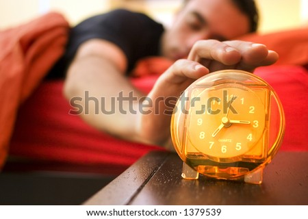 man waking up and snoozing the alarm - stock photo