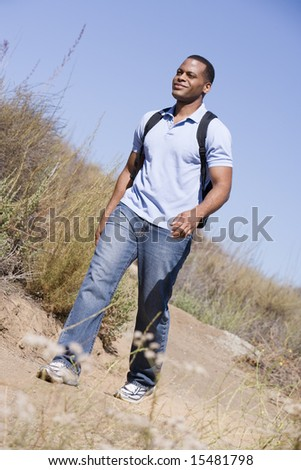 Man walking a trail in the countryside. - stock photo