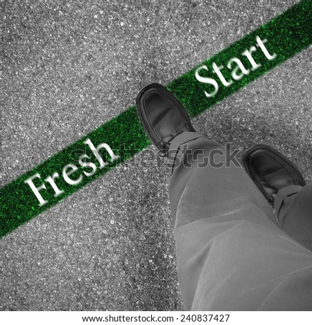 Man walking across a green line with words fresh start - stock photo