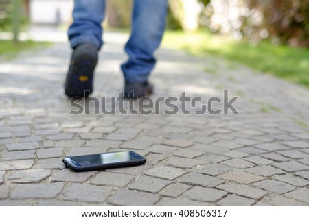 Man walking after losing his smart-phone - stock photo