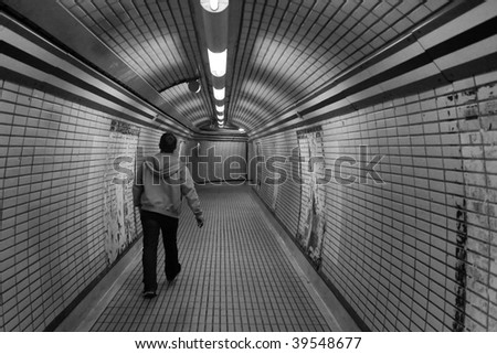 Man walking alone through a tunnel in the London Underground - stock photo