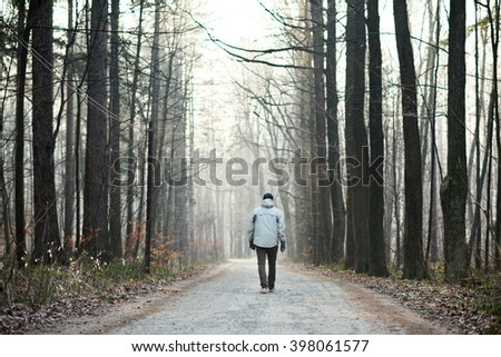 Man walking away down road between trees in winter forest - stock photo