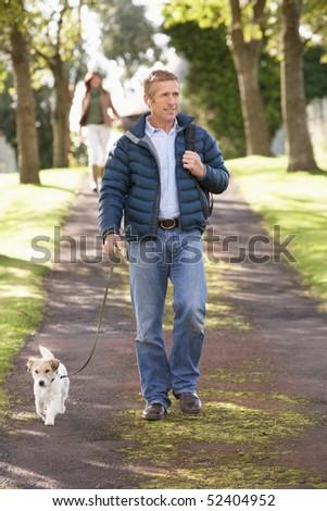 Man Walking Dog Outdoors In Autumn Park - stock photo