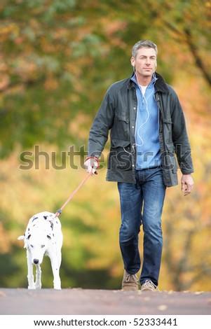 Man Walking Dog Through Autumn Park Listening to MP3 Player - stock photo