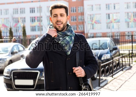 man walking down the street with a bag on his shoulder - stock photo