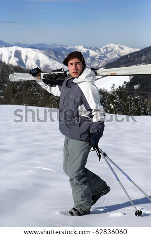 Man walking in snow carrying skis on his shoulder - stock photo