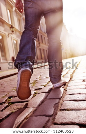 Man walking into bright light - stock photo