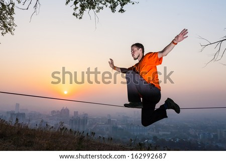 Man walking on a tightrope at sunset slack-line - stock photo