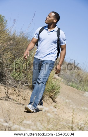 Man walking on path to beach - stock photo