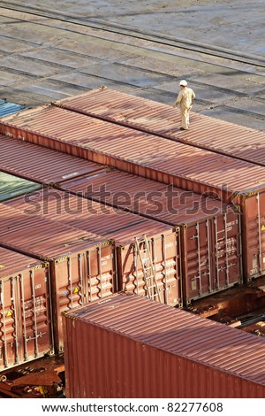 man walking on shipping containers, overhead view - stock photo