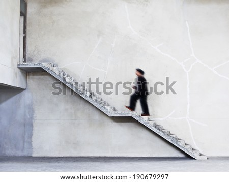 man walking on stairs to the door on cement wall background - stock photo