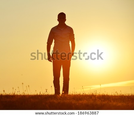 Man walking on summer sunset meadow - stock photo