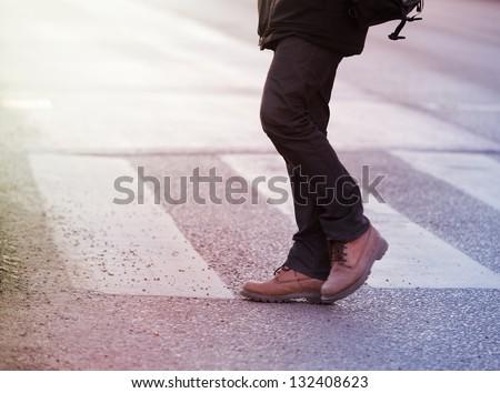 Man walking on zebra crossing - stock photo
