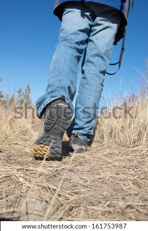 Man walking or running on trail in nature outdoors, sport shoes and exercising on footpath - stock photo