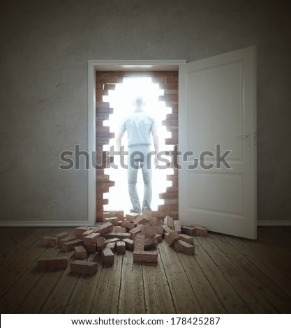 Man walking through an opening in a brick wall blocking the doorway - stock photo