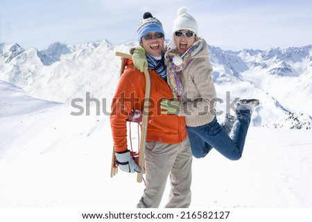 Man walking through snow carrying a sled on his back and lifting girlfriend - stock photo