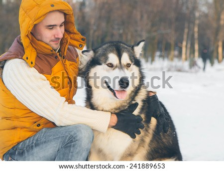 Man walking with dog winter time with snow in forest Malamute and Huskies friendship - stock photo