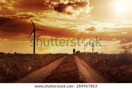 Man walking with his dog on the field with windmills. Emotional sepia background - stock photo