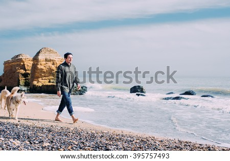 man walking with siberian husky and labrador dog on beach - stock photo