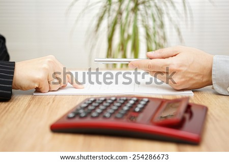 Man wants a woman to sign a contract, woman wants correction on contract - stock photo