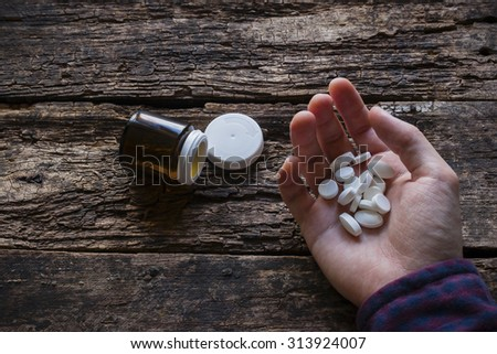 man wants to commit suicide by eating pills - stock photo