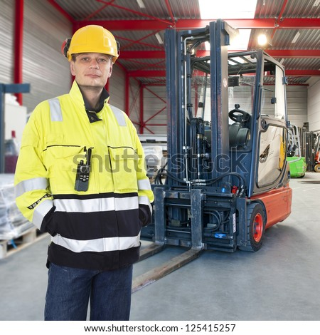 Man, waring safety clothes, including a hard hat, standing proudly in front of his forklift truck in a warehouse - stock photo