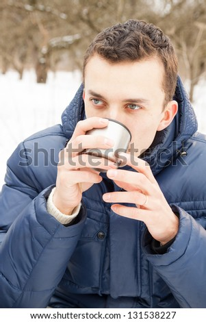 Man warming up with hot tea in cold winter time sitting - stock photo