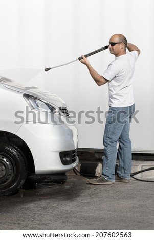 Man washes his car with water pressure cleaner - stock photo