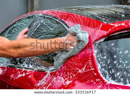 Man washing a red car - stock photo