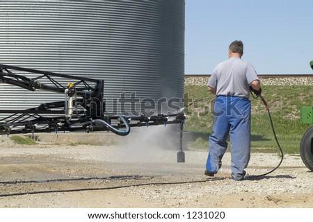 man washing a spray boom - stock photo