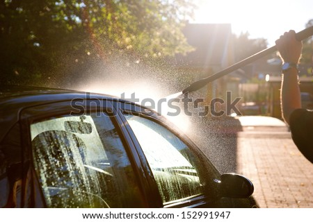 man washing car in sunshine with high pressure washer - stock photo