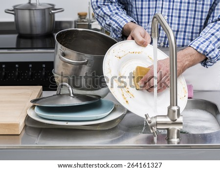 Man washing dishes in kitchen sink - stock photo
