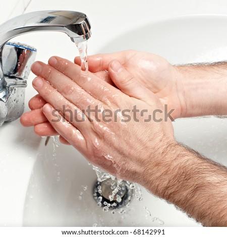 man washing hands under running water - stock photo
