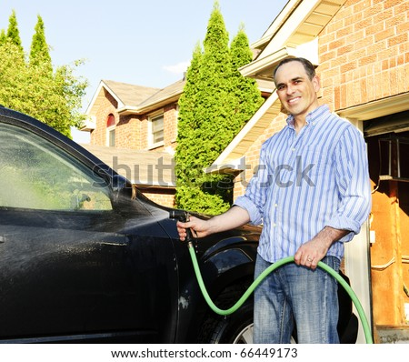 Man washing his car on the driveway - stock photo